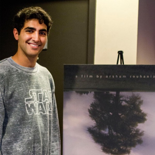 Arshum standing next to his A Day with God poster on the night of the film's premiere.